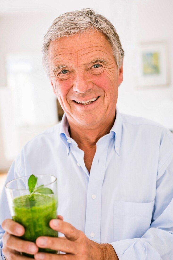 Älterer Mann hält Glas mit grünem Smoothie in der Hand