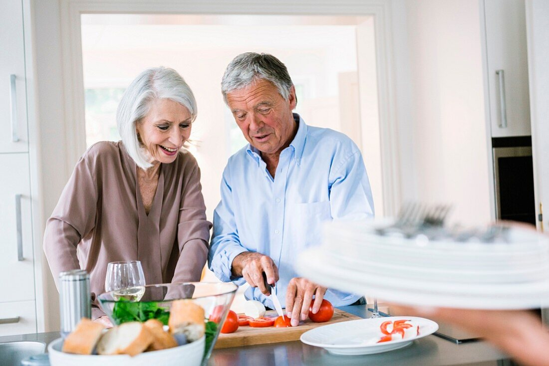 An older couple cooking together in the kitchen