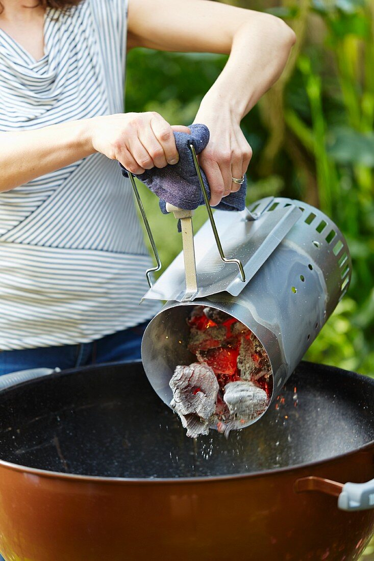 A woman tipping glowing charcoal from a chimney starter into a kettle grill