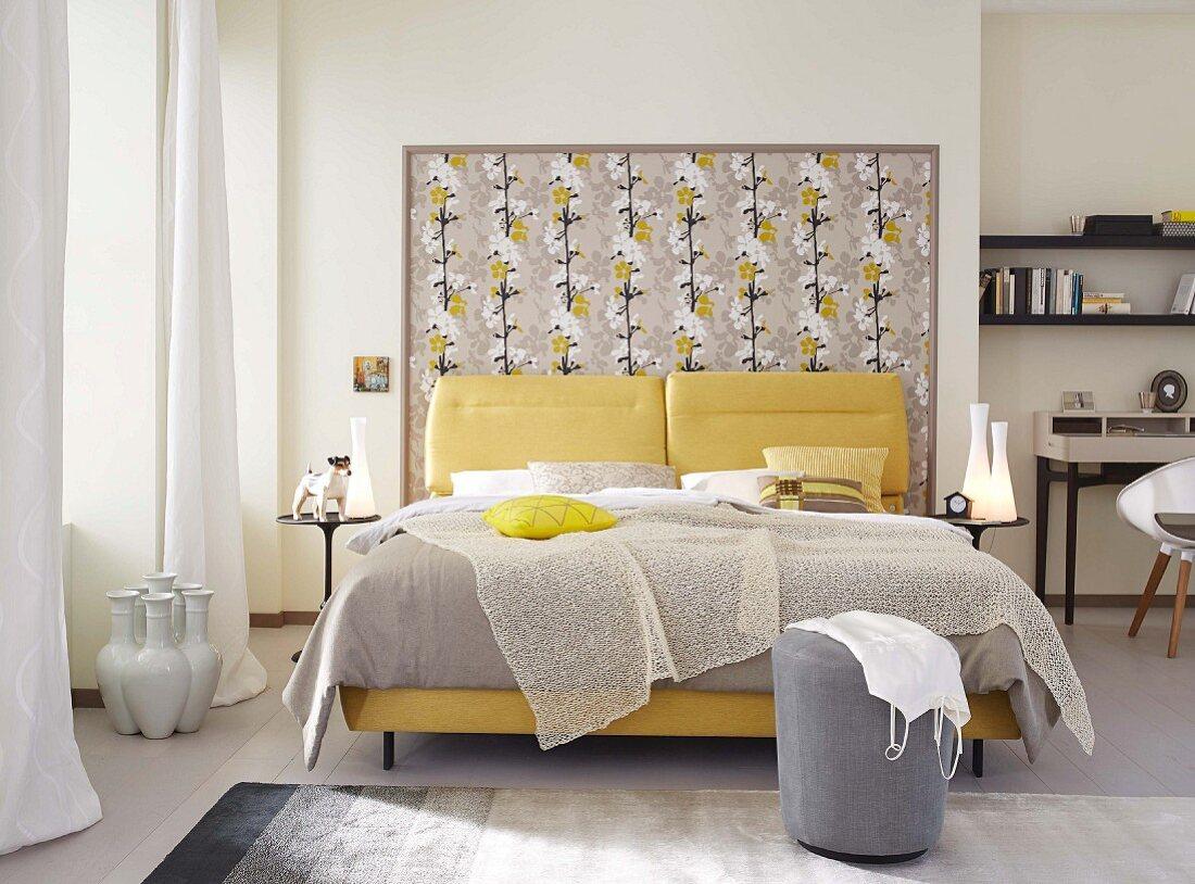 Elegantes, feminines Doppelbett mit luftigem Plaid und gelben Polstern vor blumig tapeziertem Rahmen am Bettkopfende