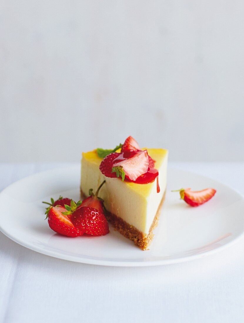 A slice of New York cheesecake with strawberry sauce and fresh strawberries