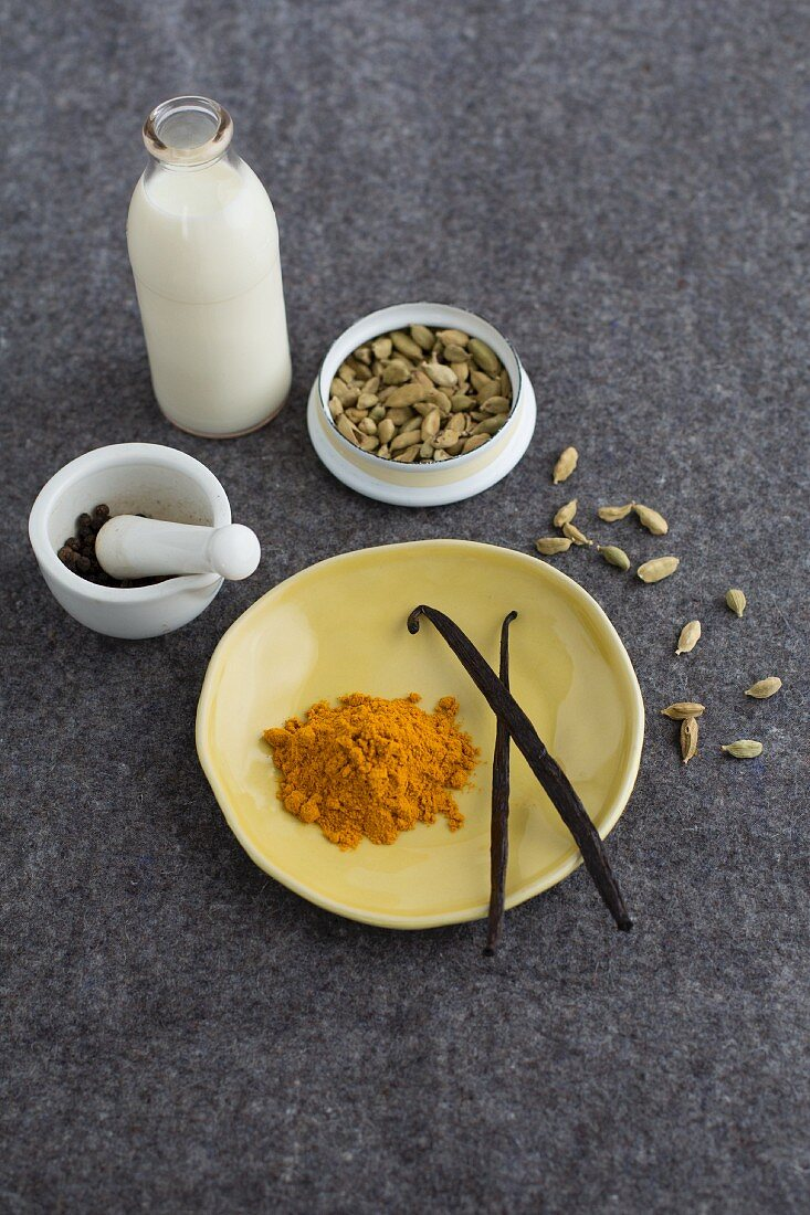 A small bottle of milk with a porcelain mortar, vanilla pods, cardamom pods and turmeric