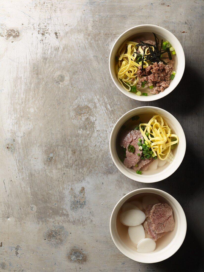 Dduk Guk (rice cake soup with beet, nori and omelette strips, Korea)