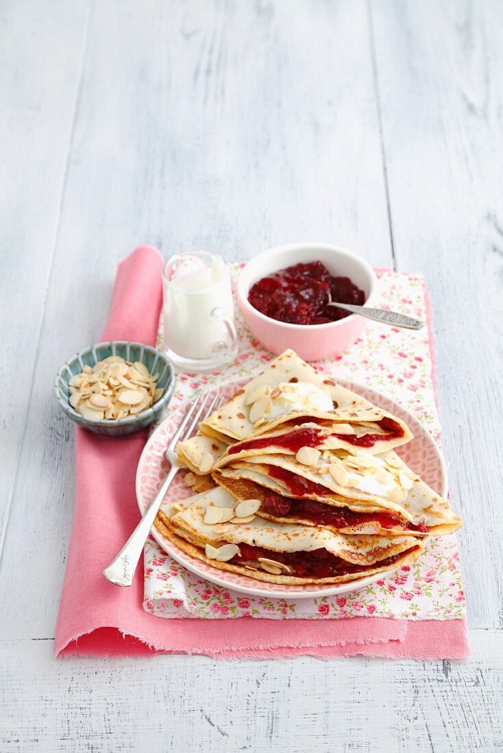 Pancakes with cherry jam, yoghurt and flaked almonds