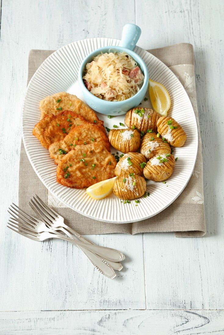 Breaded pork escalope switch Hasselback potatoes and sauerkraut