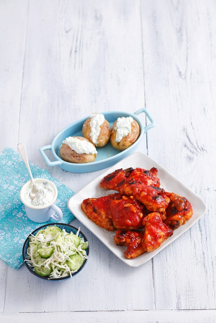 Barbecue chicken wings and legs, coleslaw with cucumbers, and jacket potatoes with tzatziki