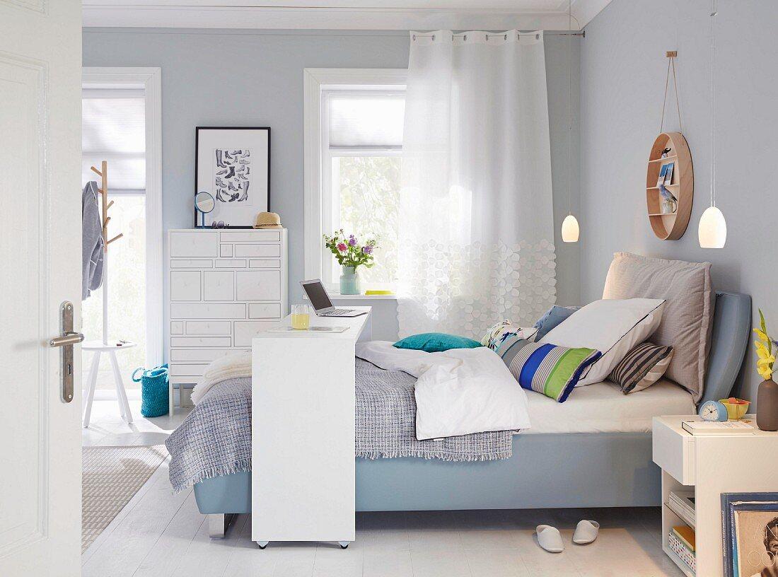 Boxspringbett mit Brettbrücke im Schlafzimmer in Blautönen