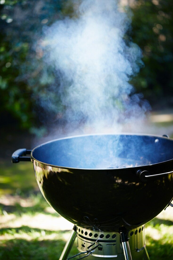 A smoking kettle barbecue