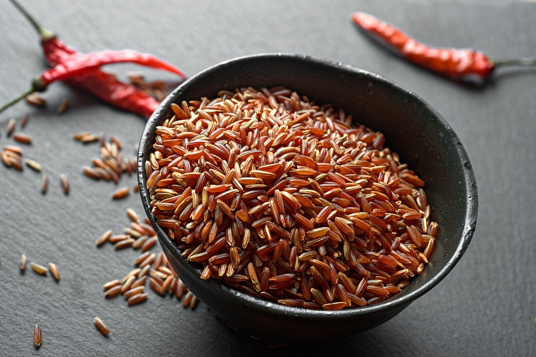 A bowl of red rice with chilli peppers in the background