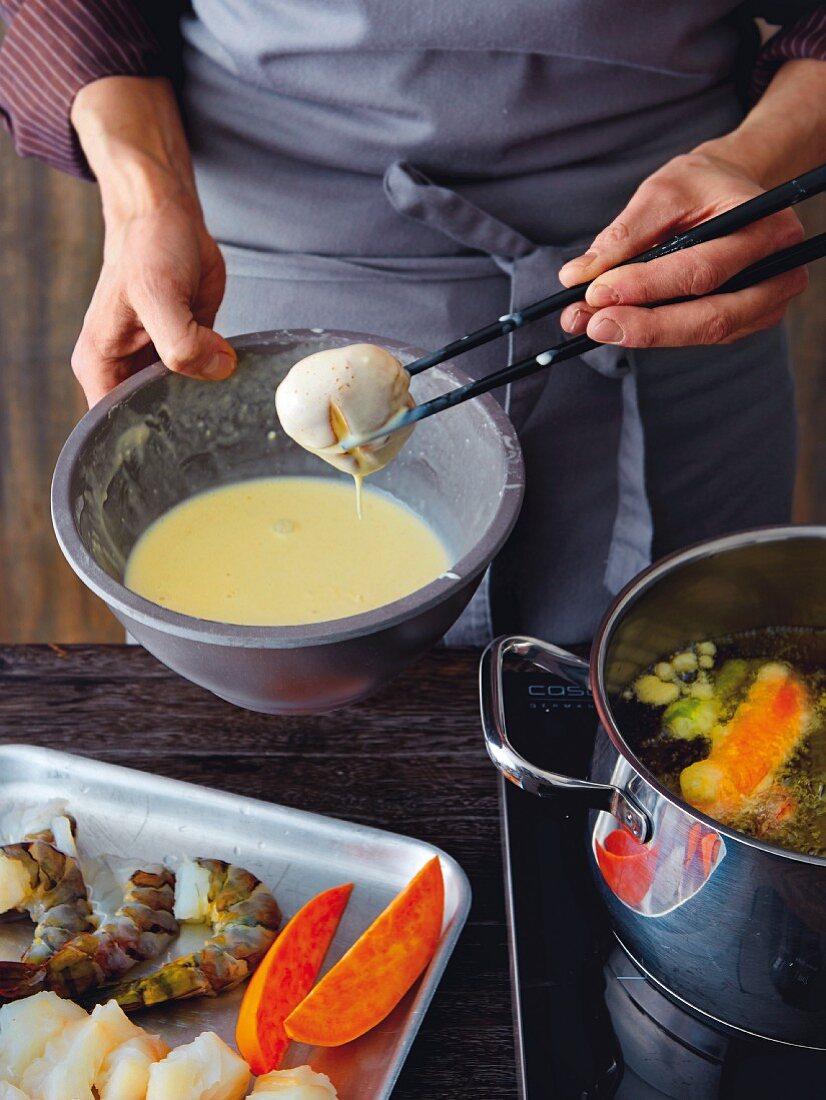 Tempura with vegetables and prawns: mushrooms being dipped in tempura batter