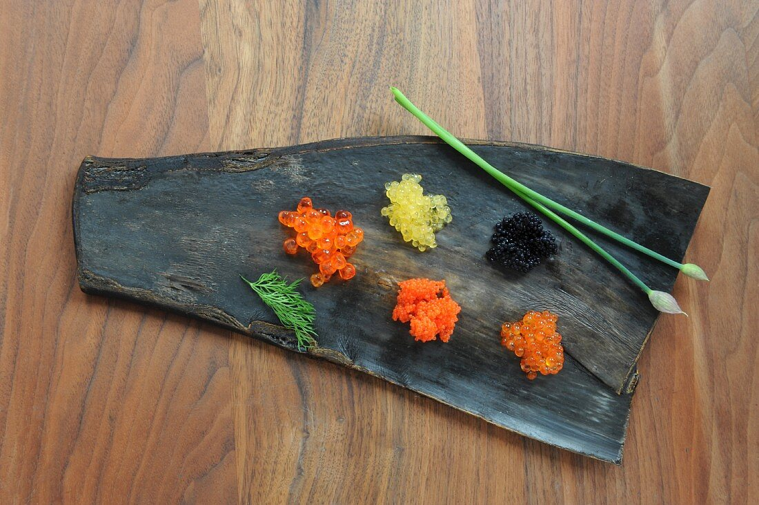 Various types of caviar on a leaf