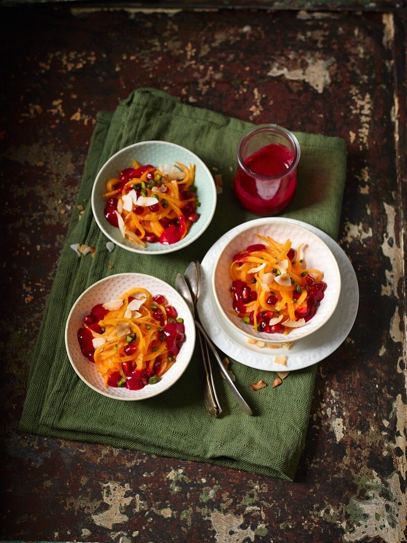 Persimmon salad with pomegranate seeds, coconut, pistachios and berry sauce