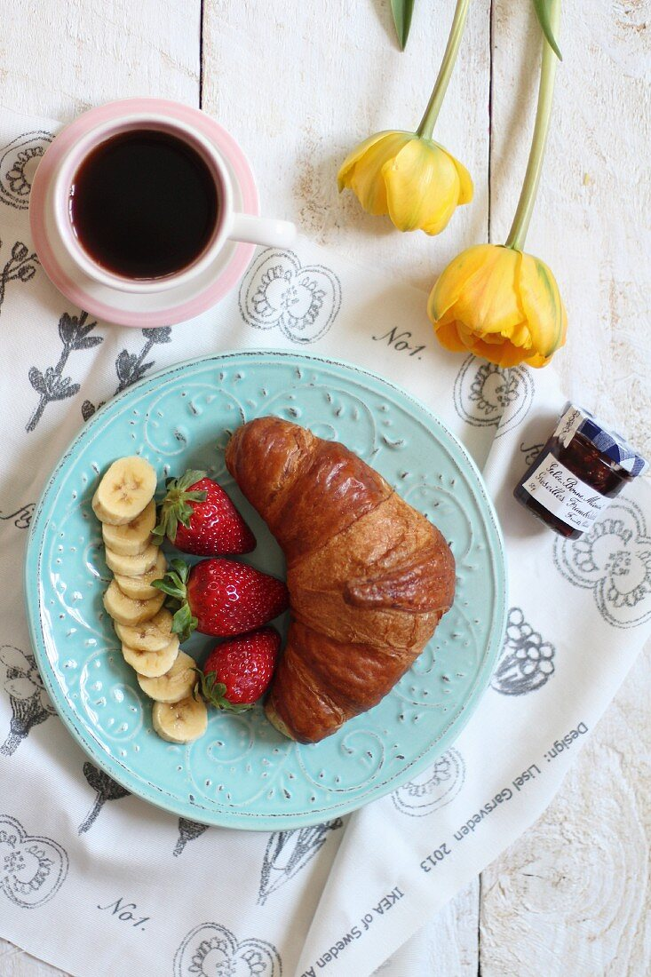 A sweet breakfast with a croissant, fruit, jam and coffee