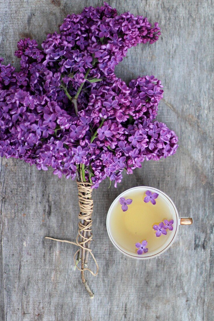 A bunch of purple lilac next cup of tea with lilac flowers