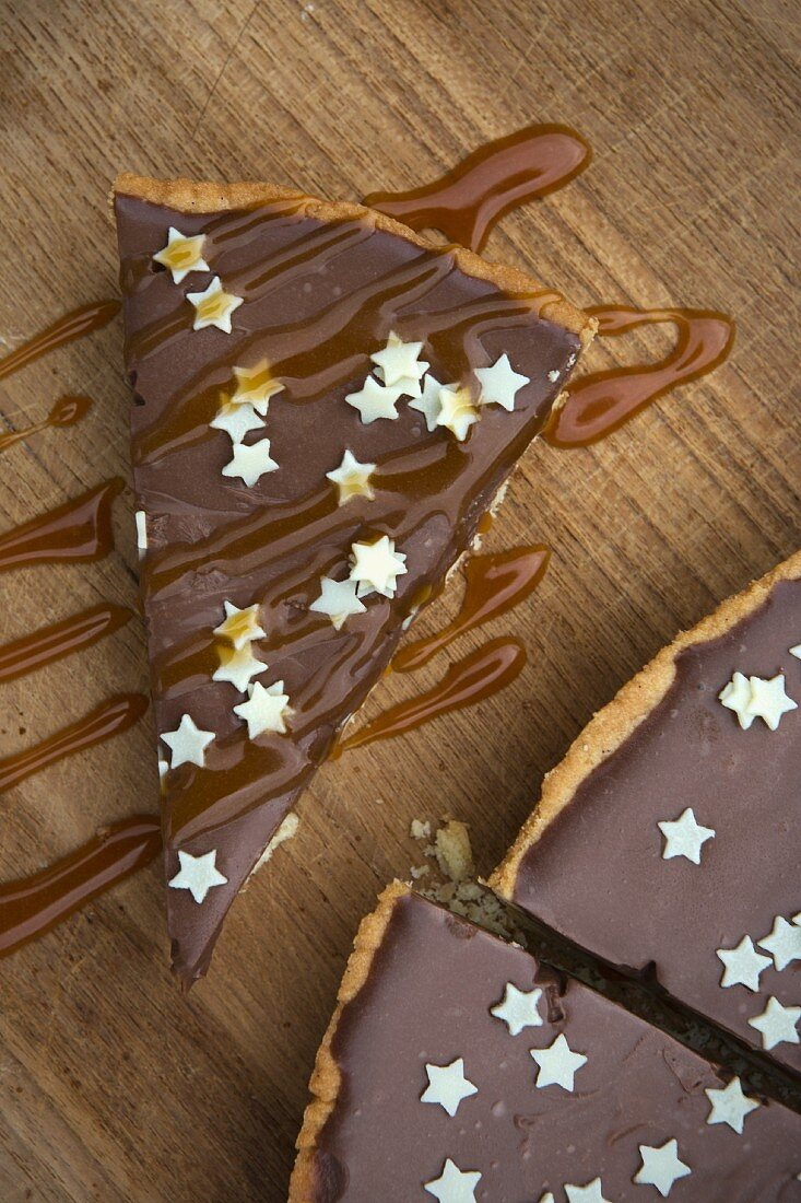 Tarte au chocolat decorated with small white stars and caramel sauce on a wooden board