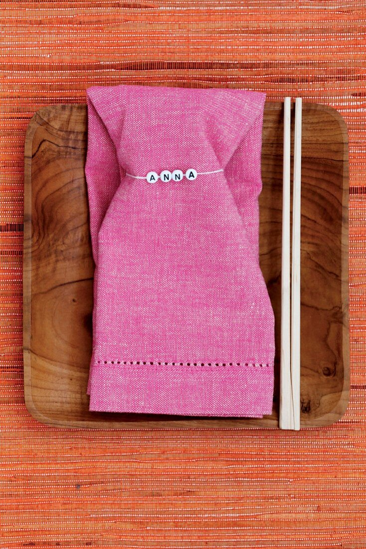 Pink linen napkin with name tag and chopsticks on wooden dish
