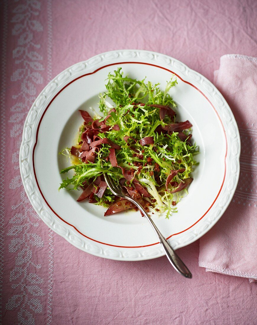 Frisee lettuce with wild boar ham