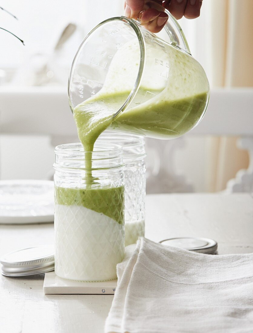A green smoothie with avocado and matcha being poured over yoghurt in a glass