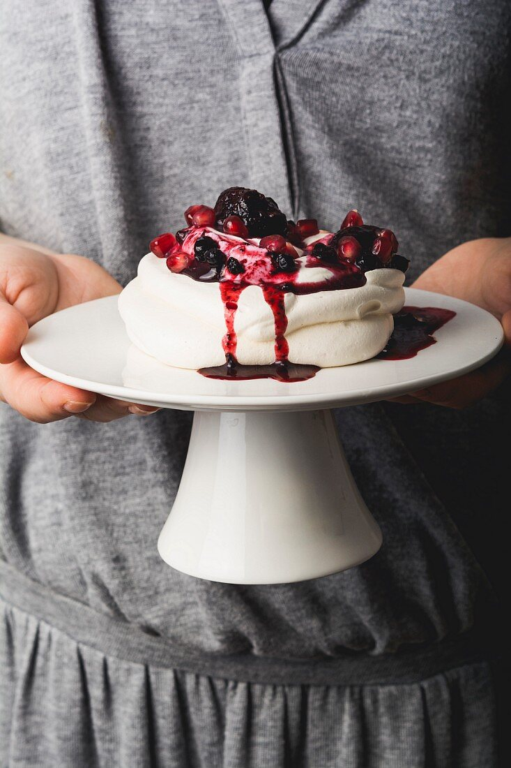 A girl holding pavlova with berries on a cake stand