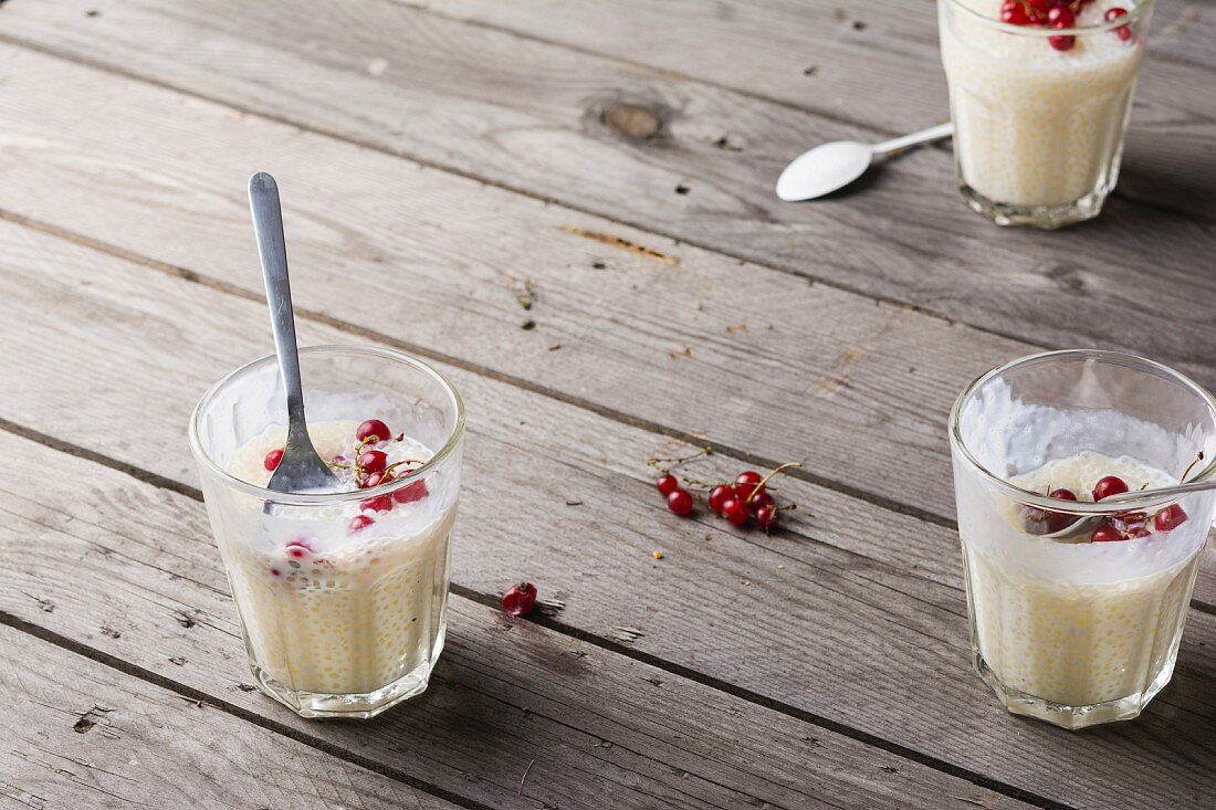 Tapioca pudding with redcurrants in glasses with spoons