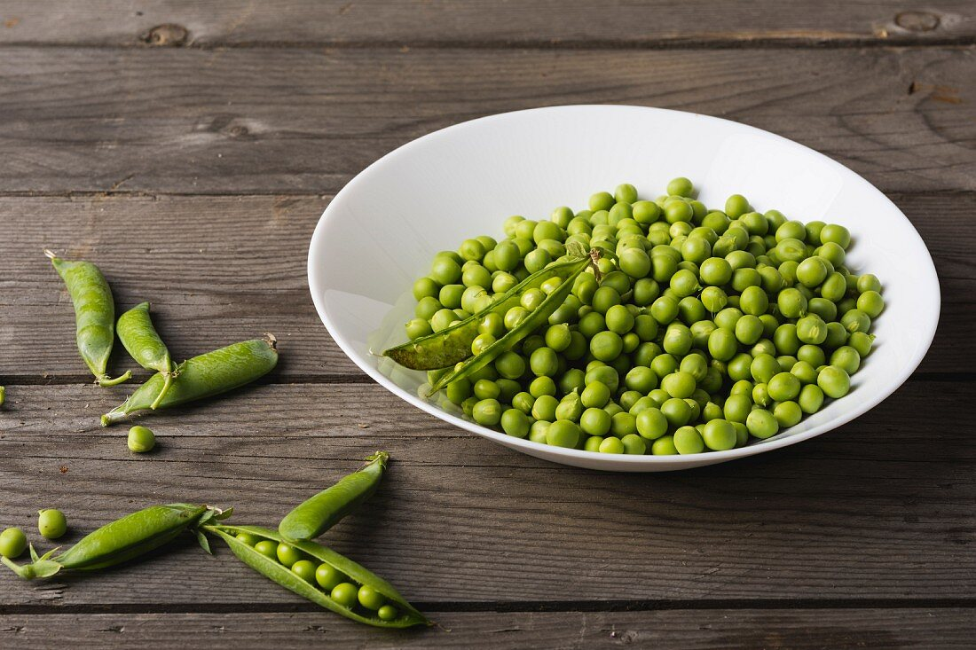 A bowl of peas and pea pods next to it