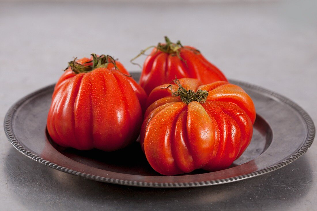 Three beefsteak tomatoes on a metal plate