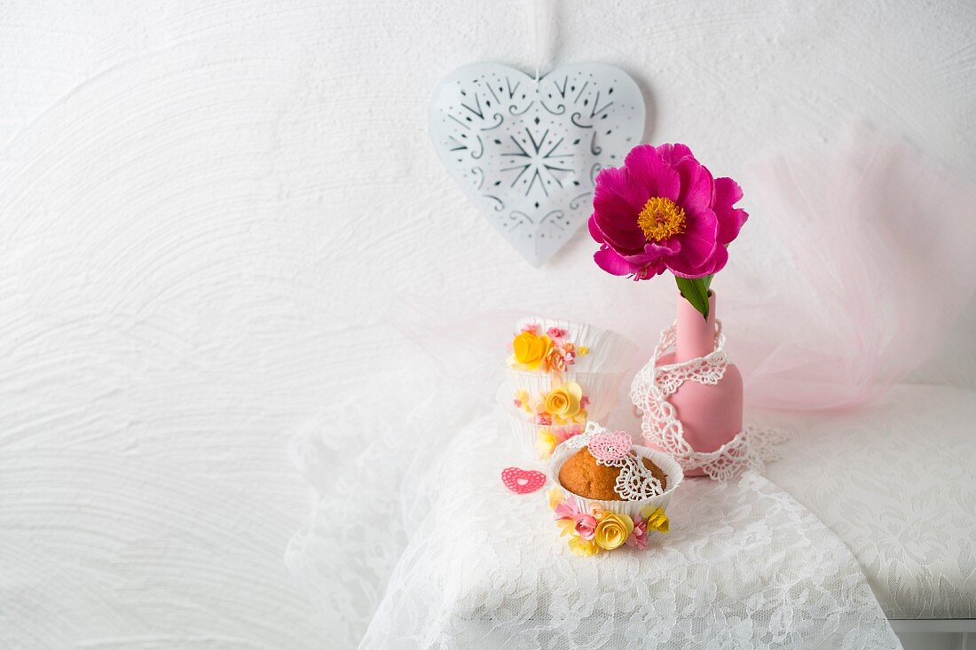 A cupcake decorated with paper flowers in front of a peoney in a vase and a decorative heart