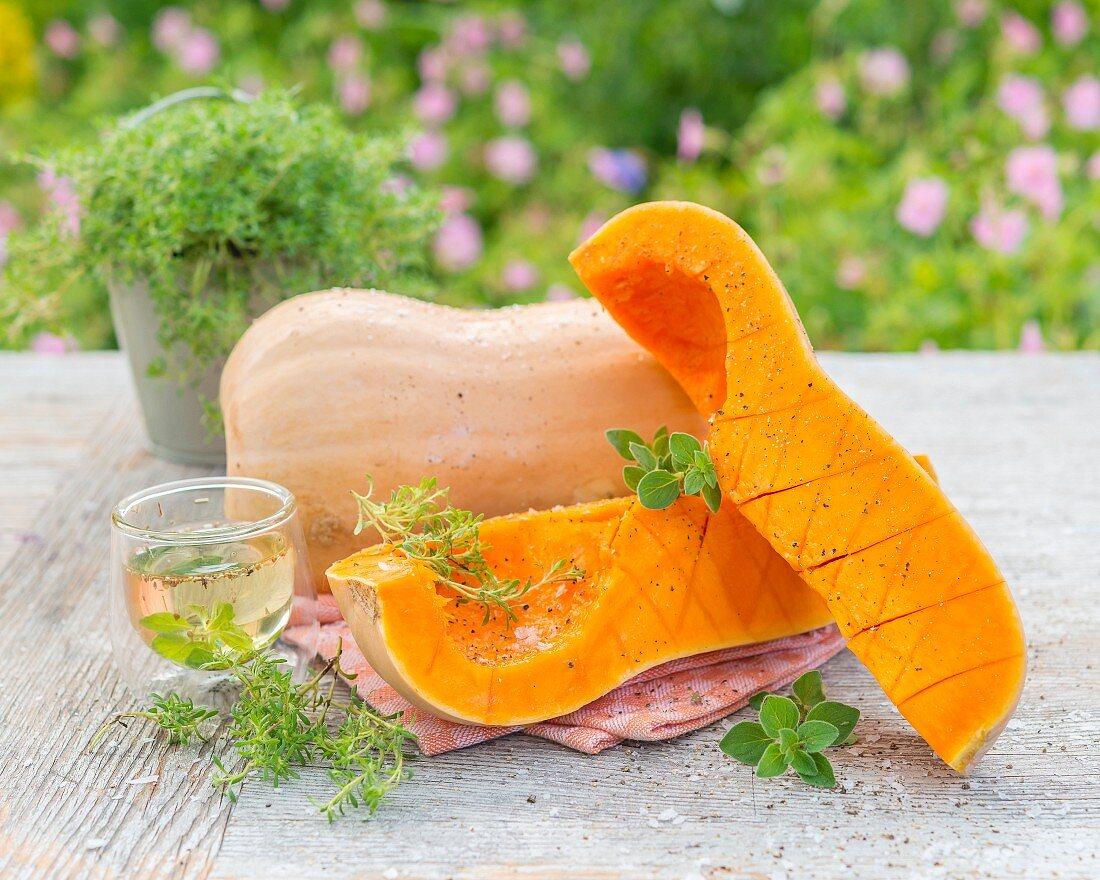 Butternusskürbis ganz und geviertelt mit Kräuteröl