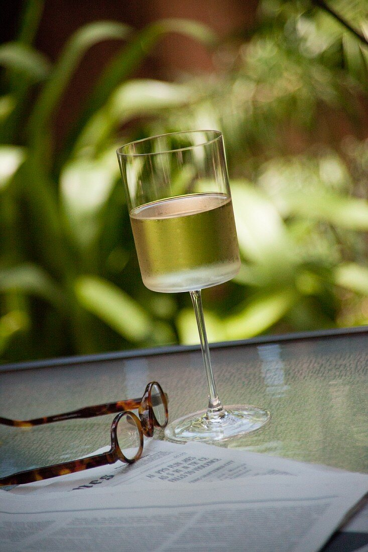 A glass of wine and a newspaper on a garden table