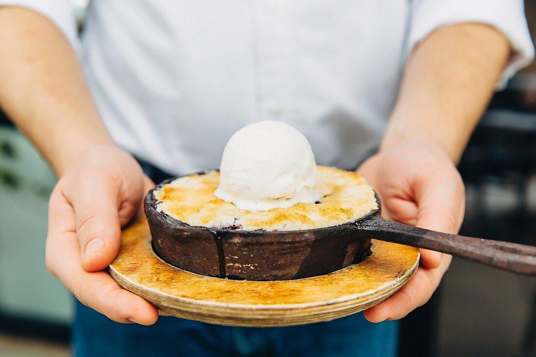 A waiter holding a small pan of dessert