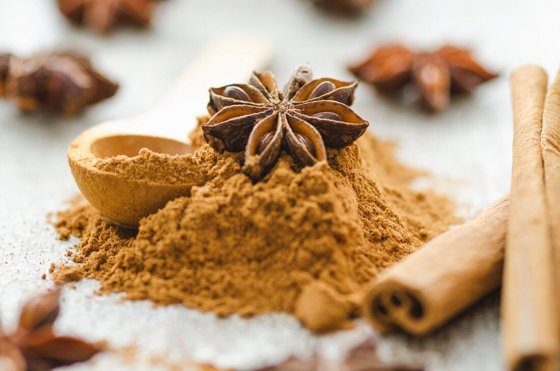 An arrangement of cinnamon sticks, ground cinnamon and star anise (close-up)
