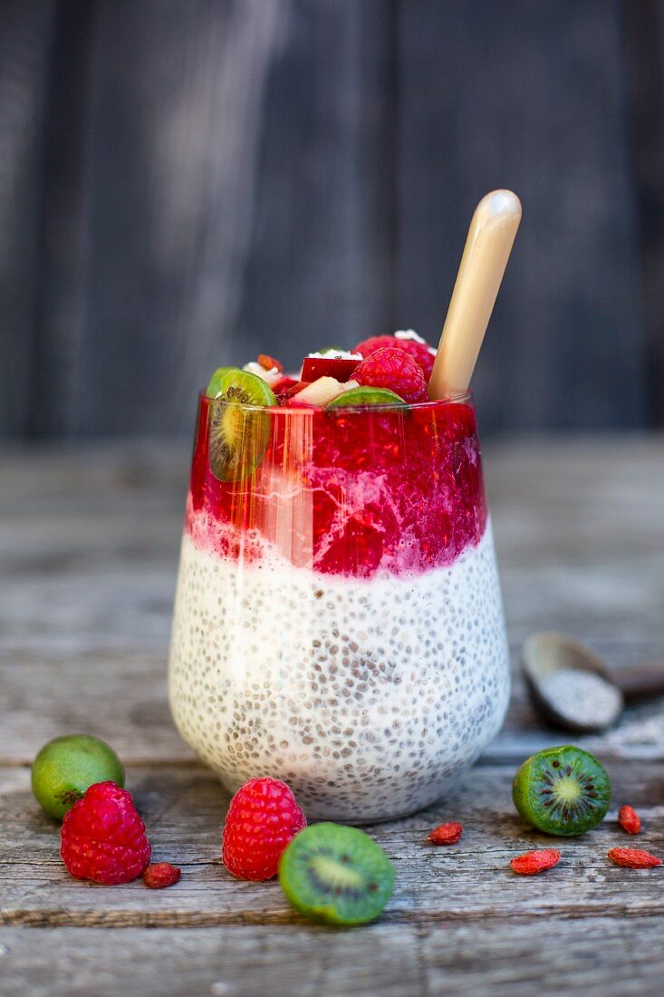 A glass of chia pudding with coconut, raspberry sauce, mini kiwis and goji berries