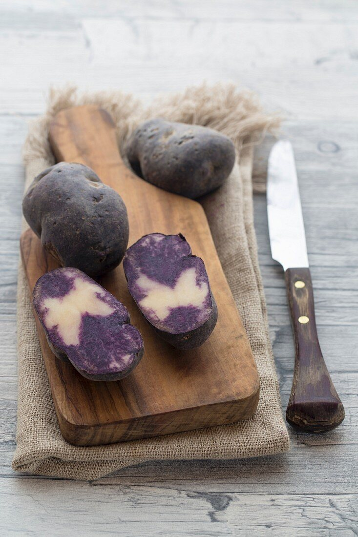 Purple potatoes, whole and halved, on a wooden board