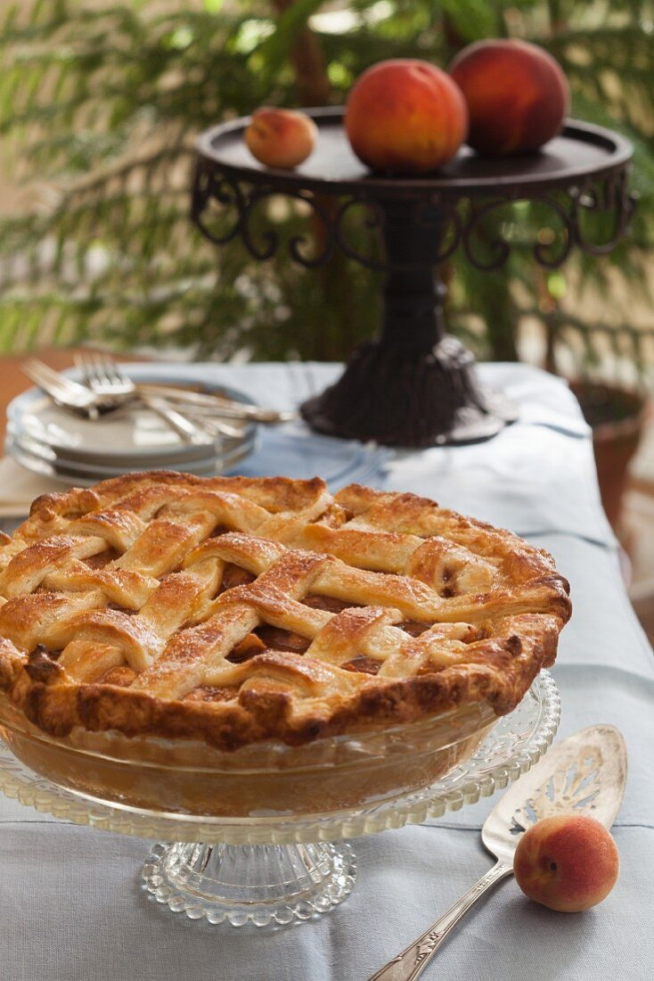 A whole peach pie with a lattice lid on a cake stand