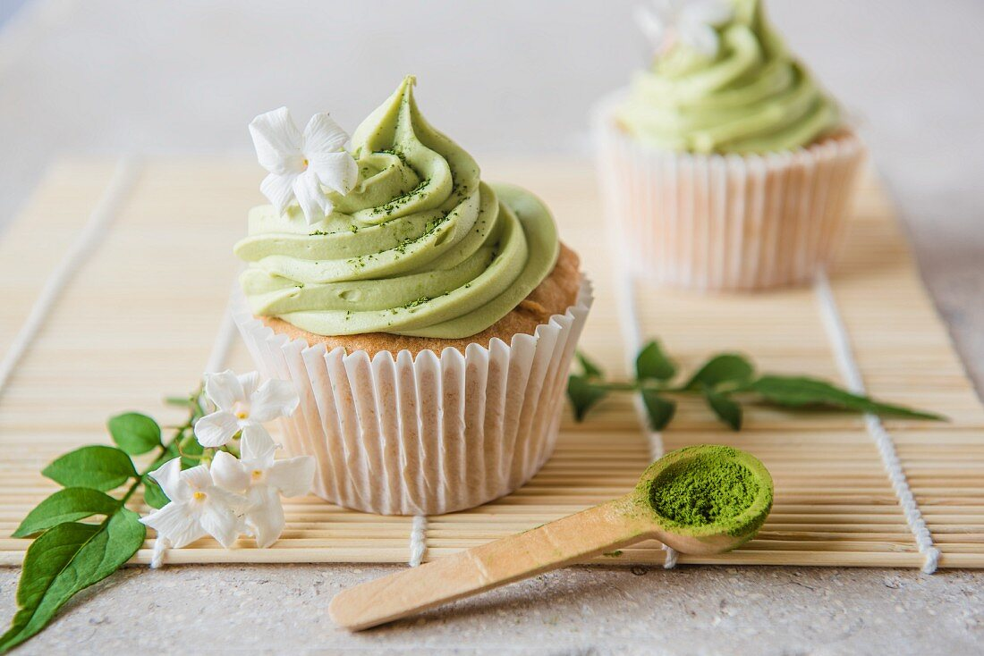 Matcha cupcakes with jasmine flowers and matcha powder on a wooden spoon
