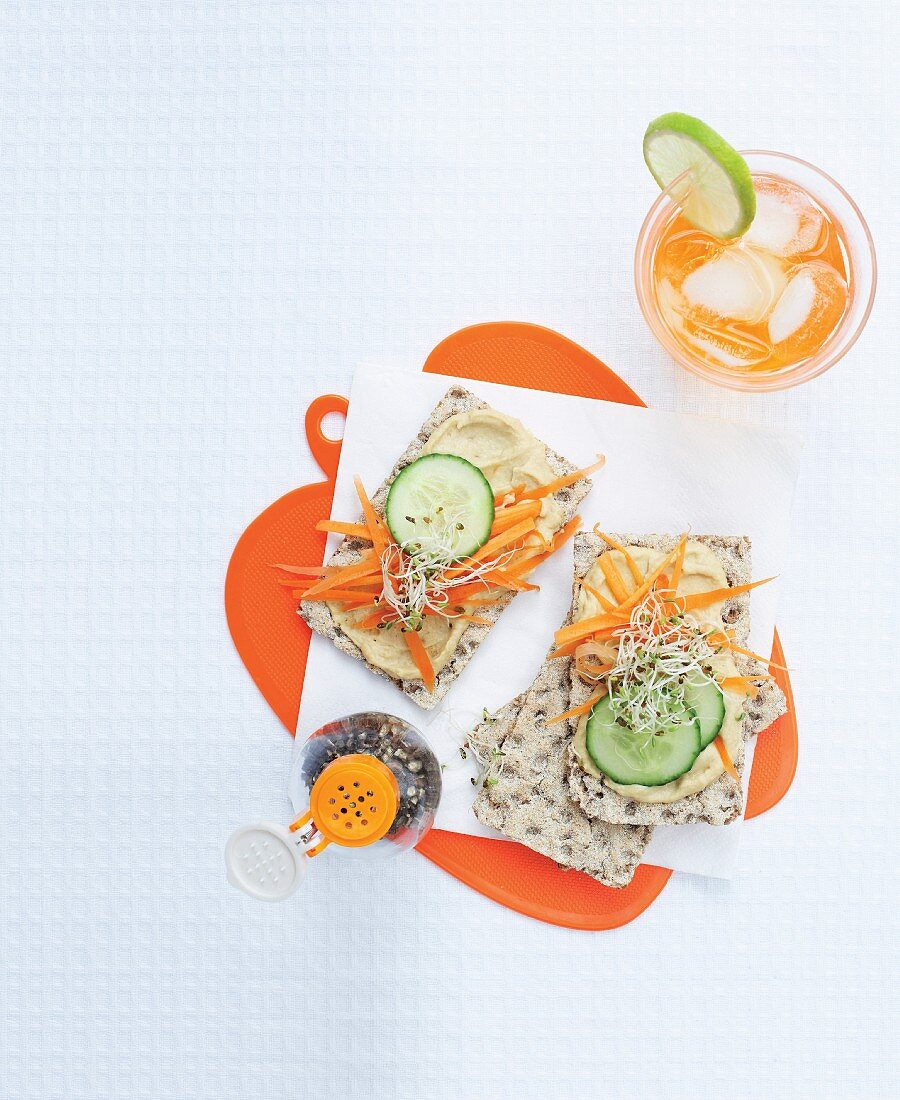 Crispbread topped with houmous, cucumber, carrots and bean sprouts