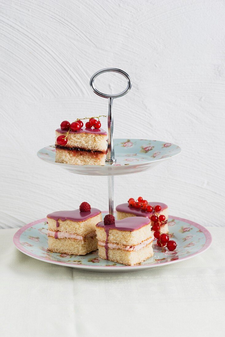 Heart-shaped sponge tartlets with raspberry cream and redcurrent jelly on a cake stand
