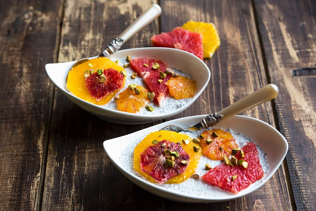 Chia pudding with orange and grapefruit slices in bowls on a wooden surface