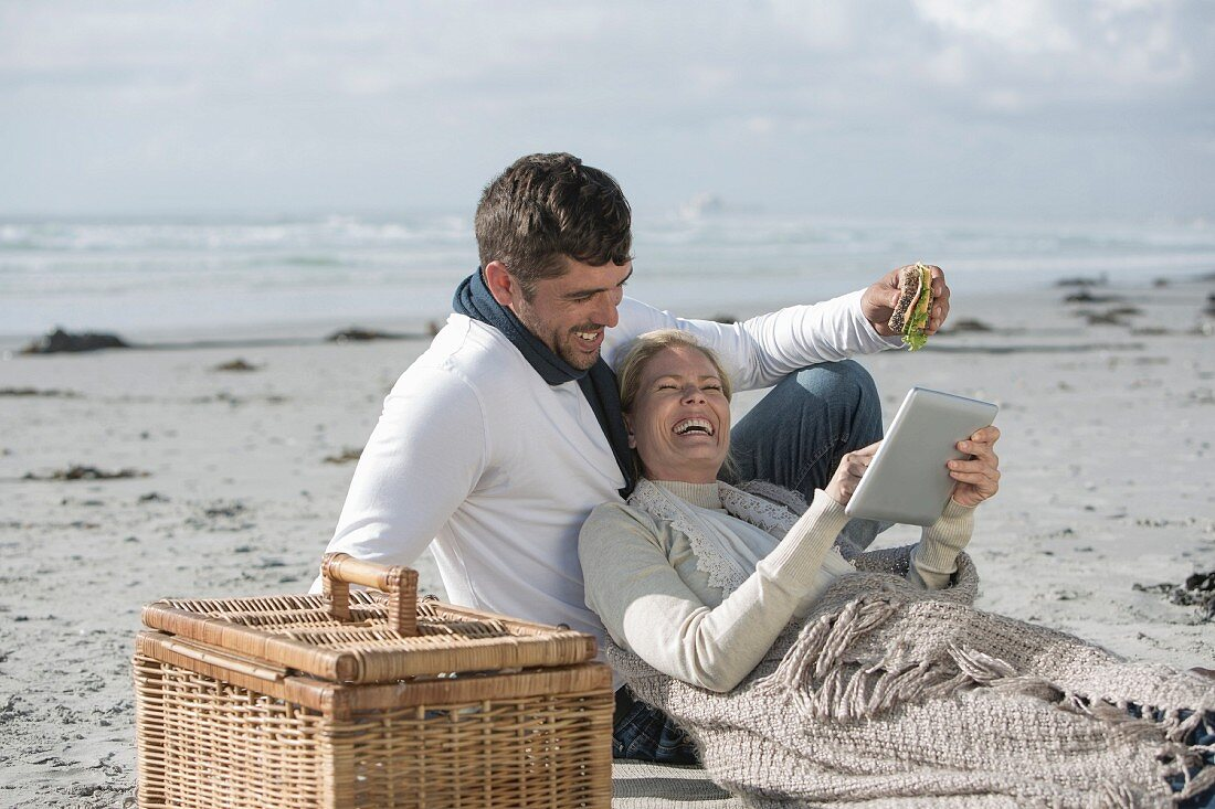 A couple sitting on a sandy beach with a tablet computer and a picnic basket