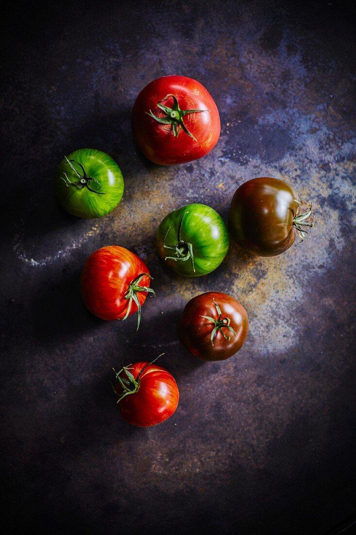 Verschiedenfarbige Tomaten auf dunklem Untergrund (Aufsicht)