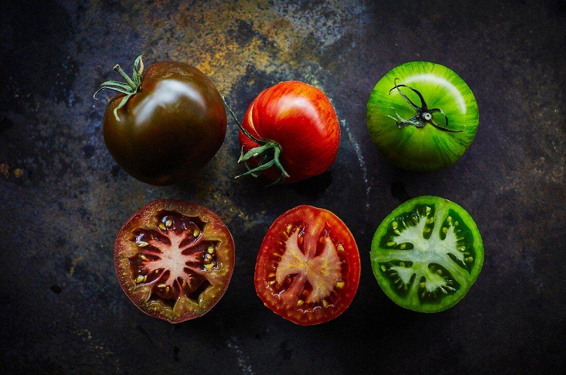 Schwarze, rote und grüne Tomate, ganz und halbiert (Aufsicht)