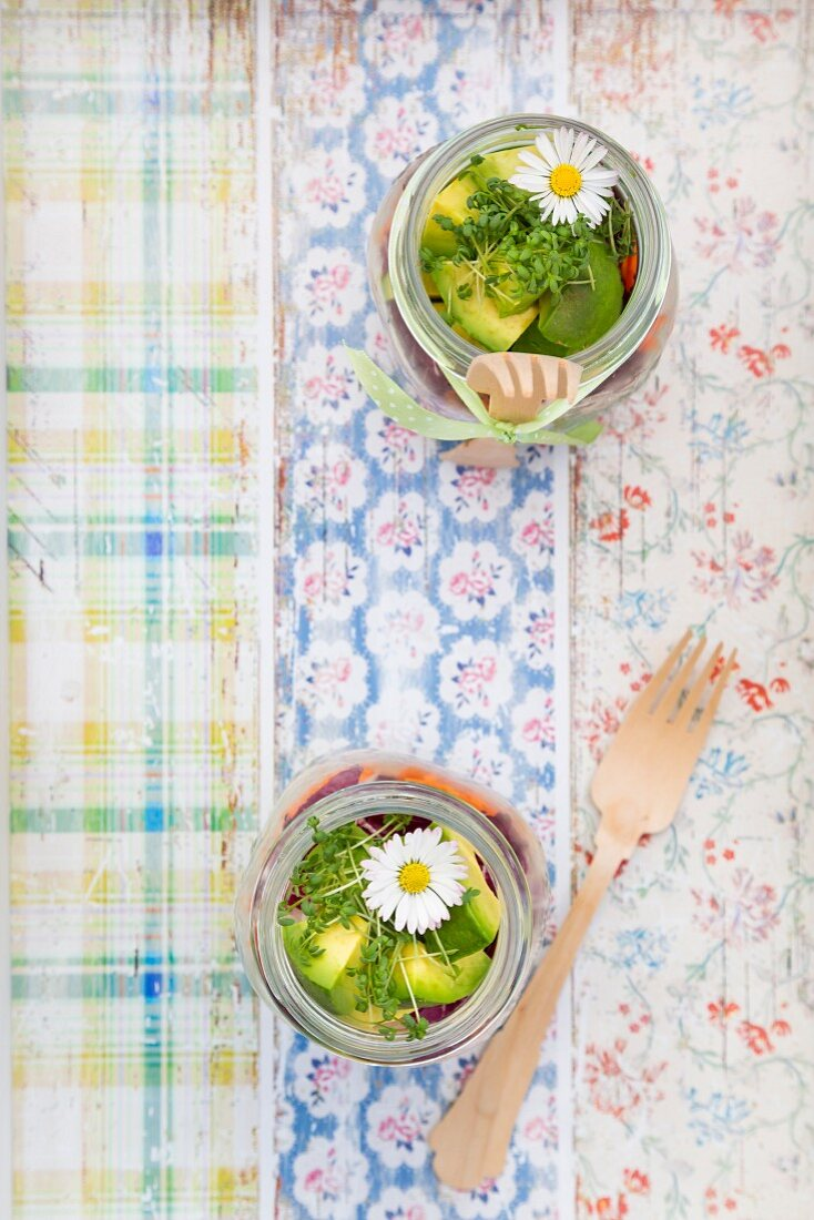 A layered spring salad with rice, vegetables and daisies in jars