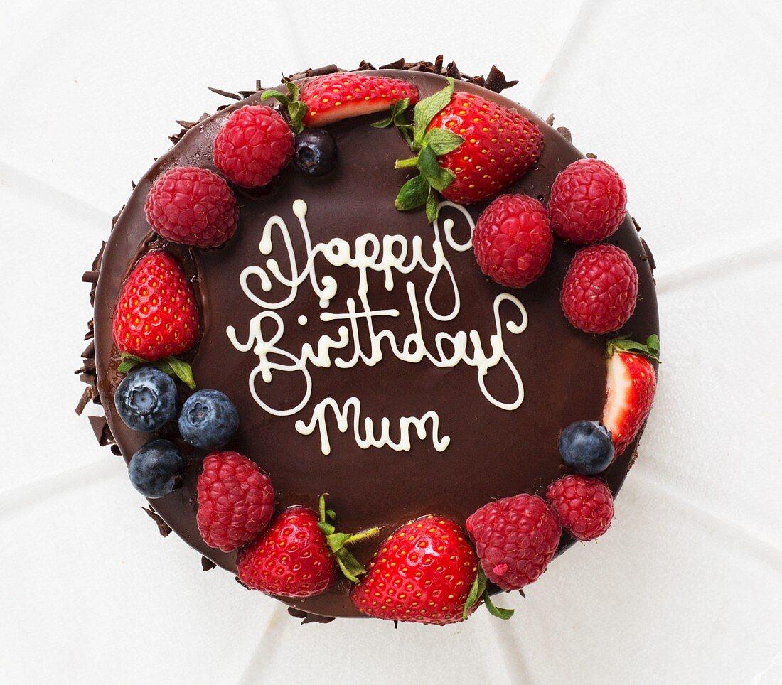 A birthday cake with chocolate glaze and fresh berries
