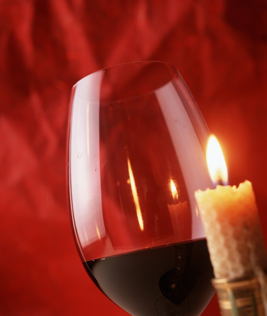 A red wine glass next to a burning candle in front of a red background
