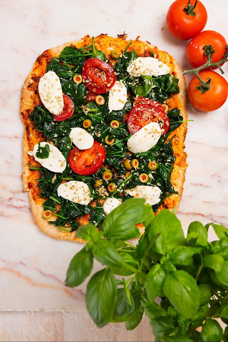 Spinach pizza with mozzarella and tomatoes