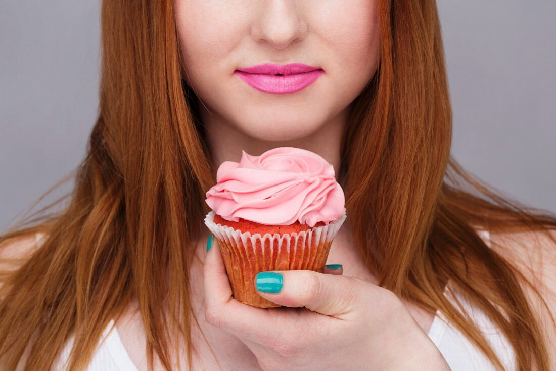 A young woman with long red hair holding a pink cupcake