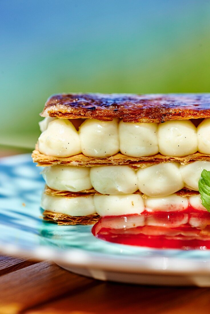 A mille feuille with vanilla rum cream and strawberry sauce