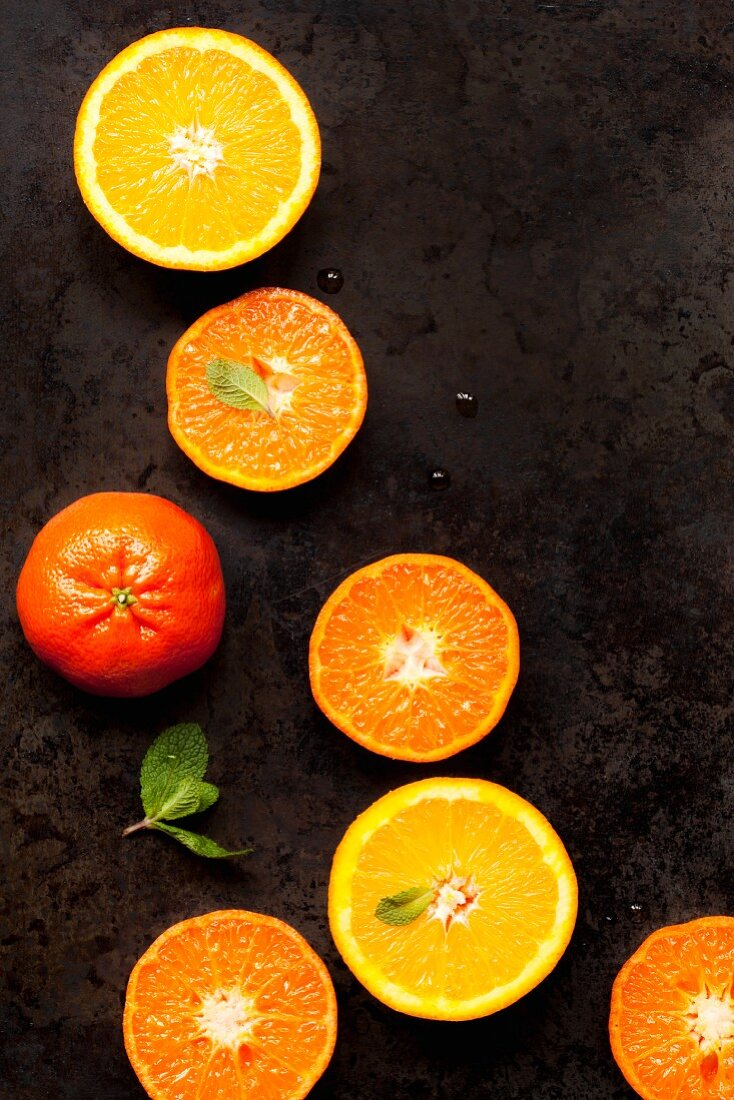 Halved oranges and clementines on a metal tray