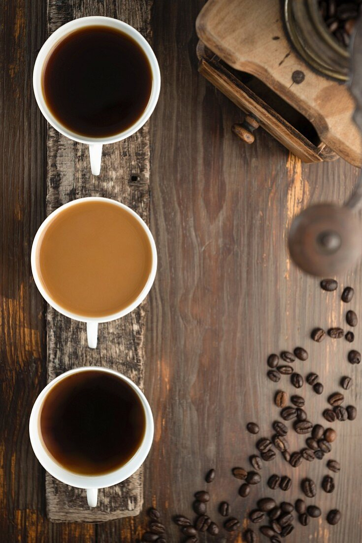 An arrangement of coffee featuring three cups of coffee, coffee beans and a coffee grinder