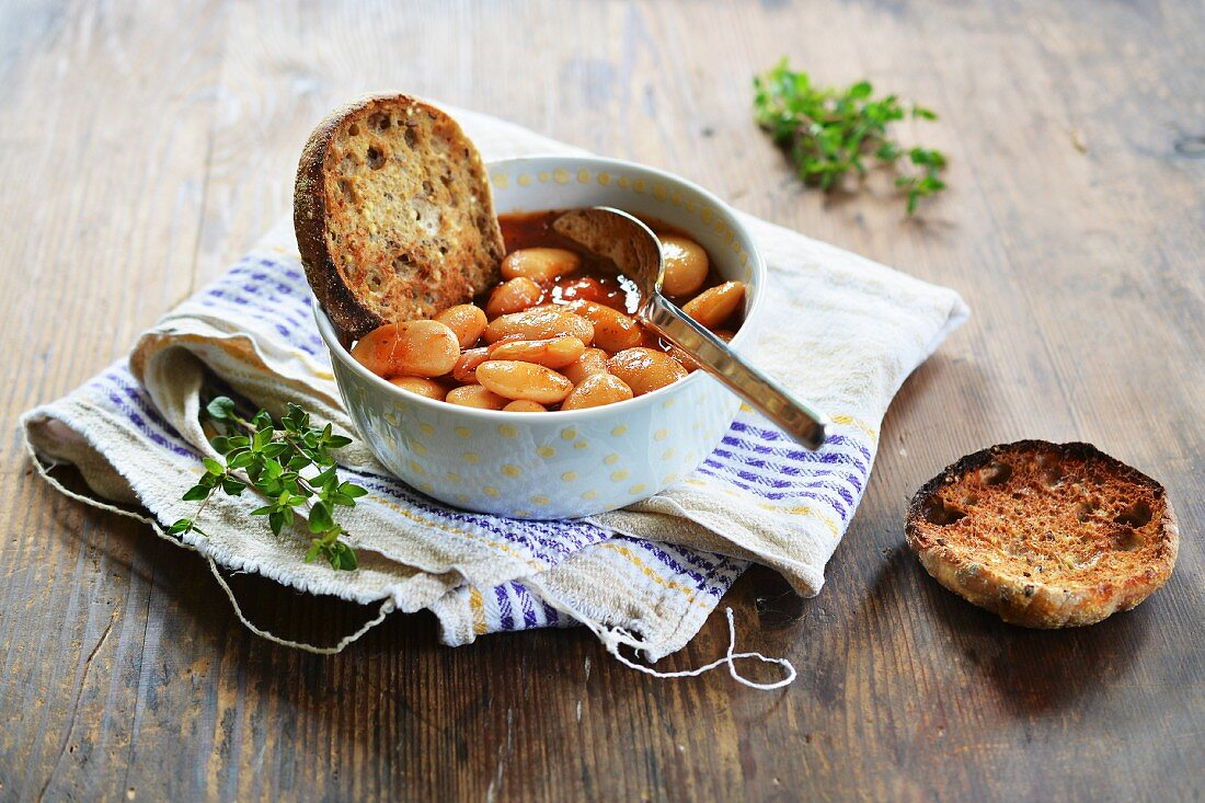Beans in tomato sauce with grilled rolls and fresh herbs